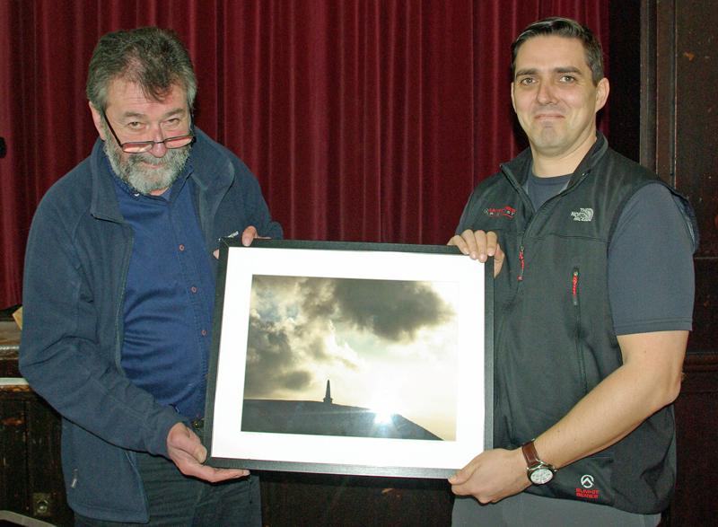 Eric Robson presents a framed landscape photograph taken by Derry Brabbs to Andrew Clayborough for winning Best in Show in the 2014 Photographic Competition. - David Johnson